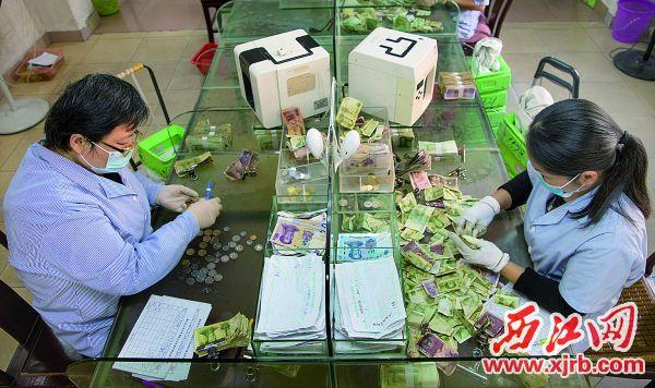 公交点钞员正在点零钞。 西江日报记者 严炯明 摄