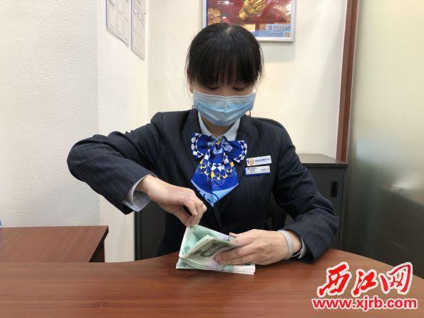 黄燕在展示她的点钞技术。杨乐祺摄