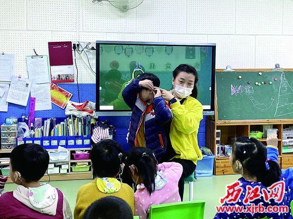 市残疾人康复中心的老师在教听障儿童戴助听器。 西江日报记者 潘粤华 摄