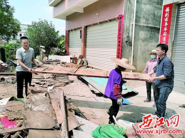 李映金(左)与村干部一起搬杂物。 西江日报通讯员 供图