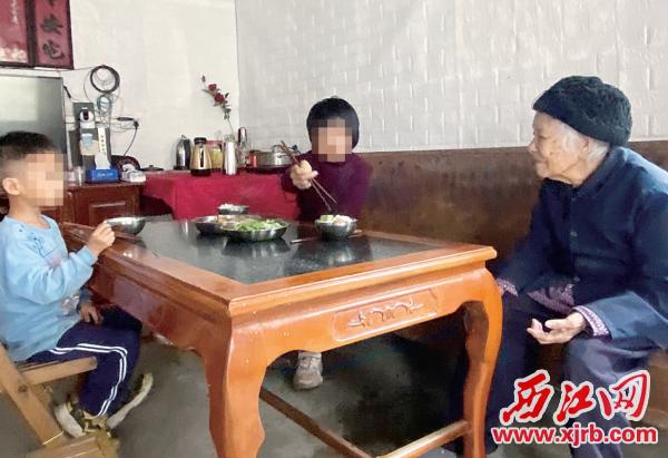 吃饭时,小茵(中间者)懂得为奶奶夹菜。 西江日报记者 赖小琴 摄