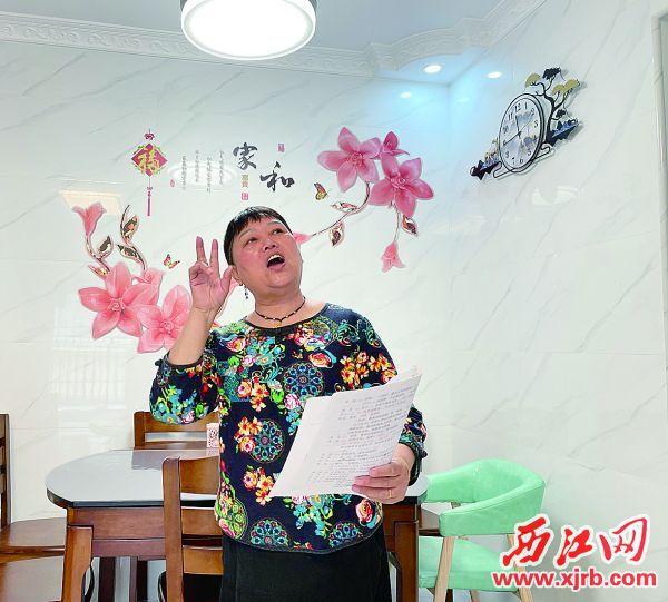 陈月莲喜欢唱山歌,在家里拿起歌谱即兴吟唱。 西江日报记者 夏紫怡 摄