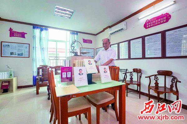 冼务金在书屋内整理书籍。 西江日报记者 曹笑 摄