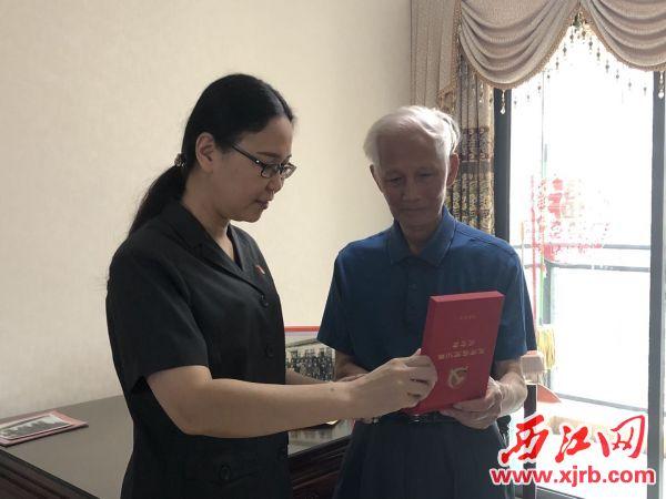 """张明老人拿到""""光荣在党50年""""纪念章。记者 万涛摄"""