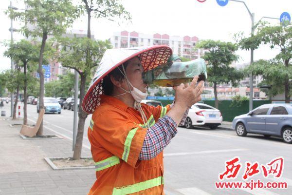 环卫工人补充水分。 记者 岑永龙 摄