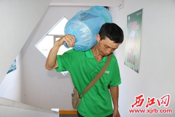 应师傅正在将桶装水送上楼。记者 李钰聿 摄