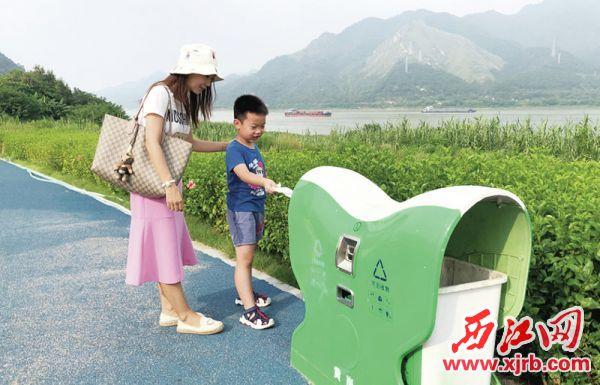 家长澳门威尼斯人捕鱼-教育小孩不要乱扔垃圾。 西江日报记者 杨乐祺 摄