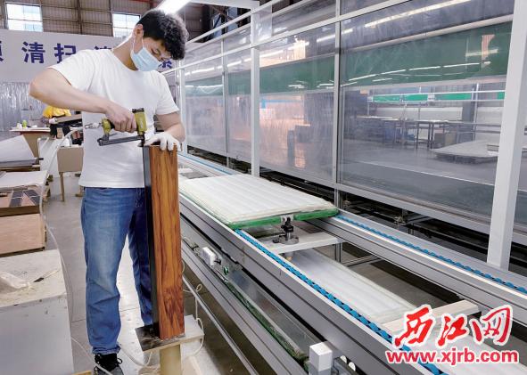 笙达音响厂房内,工人正在安装音响外壳。 西江日报记者 刘浩辉 摄
