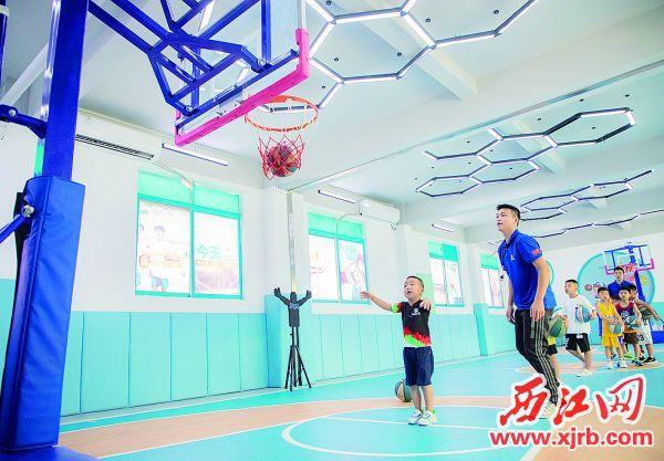 在篮球班上,小朋友练习投篮