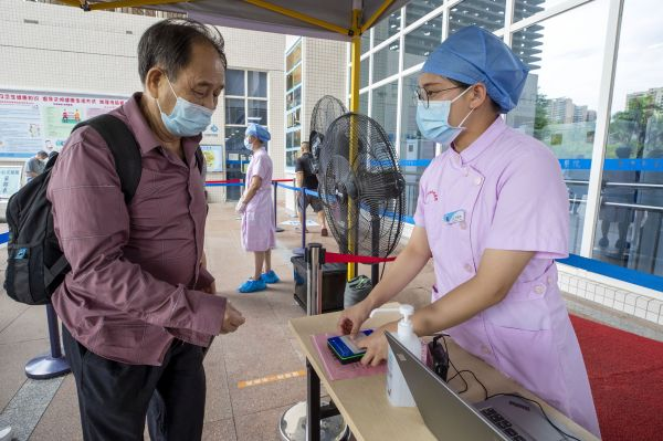 医院工作人员热心为老人刷身份证核验健康码。 西江日报记者 曹笑 摄