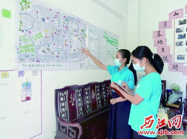 四会城中街道社工站的社工对照地图记录民政服务跟踪信息。 西江日报记者 潘粤华 摄
