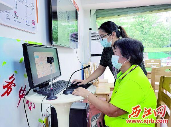中心工作人员协助社区居民进行在线问诊。 西江日报记者 潘粤华 摄